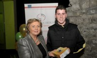 Minister Fitzgerald presents Michael Collins with a raffle prize of a digital camera