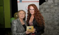 Minister Fitzgerald presents Bridget McDonagh with a raffle prize of a digital camera