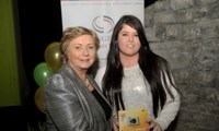 Minister Fitzgerald presents Donna Stokes with a raffle prize of a digital camera
